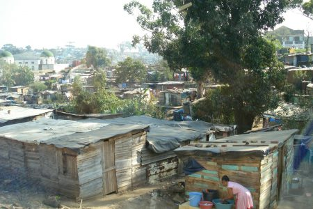 Urban slum in the developing world with woman washing clothes.