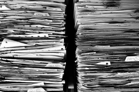 Two large piles of documents in black and white.