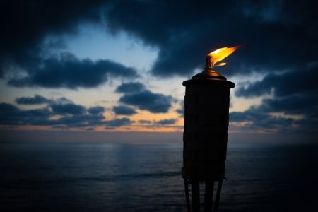 A burning torch in the night with ocean in background.