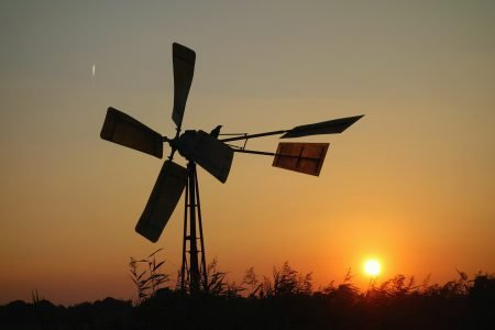 A windmill in African bush with sunset in background.