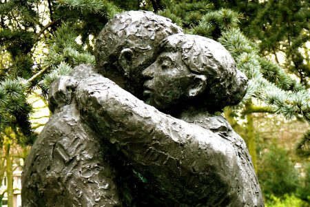 Two stone statues embracing.